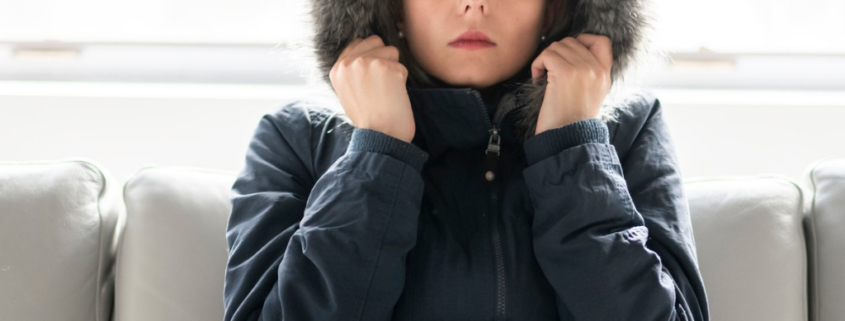 Woman in coat indoors cold due to untreated thyroid condition